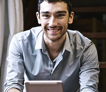 Man Smiling Reviewing Tablet